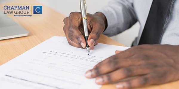 Image of a doctor signing a health care employment contract.