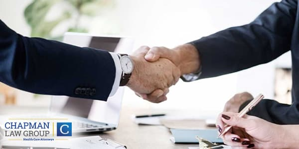Image of a doctor and a healthcare defense attorney shaking hands.