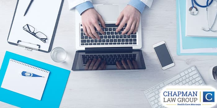 Image of a doctor in their office typing on a laptop.