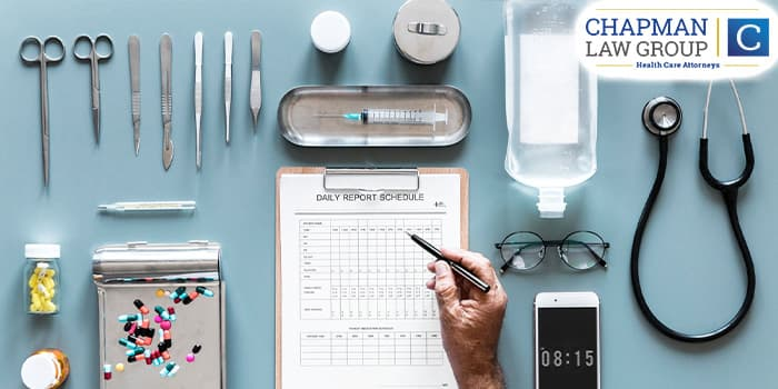 image of a table with medical equipment on it and the hand of a doctor writing on a medical form.