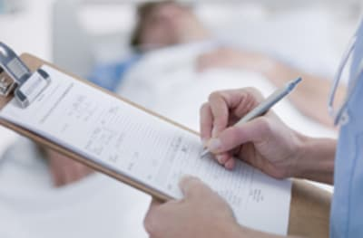 Image of a doctor filling out a form.