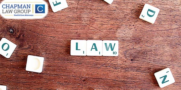 """Image of pieces from the board game """"scrabble"""" that spell out the word """"law""""."""