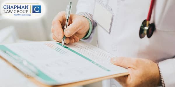 Physician writing on a form.