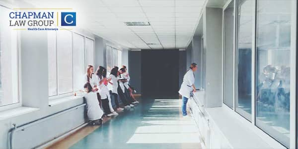 Doctors and nurses in a hallway of a hospital facing the windows on both sides.
