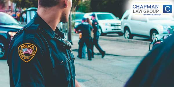 Image of a police officer watching other police officers arrest someone.
