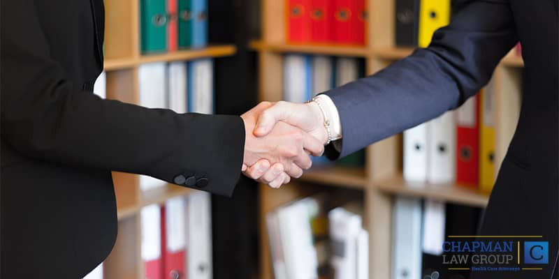 Healthcare Professional and Lawyer Shaking Hands